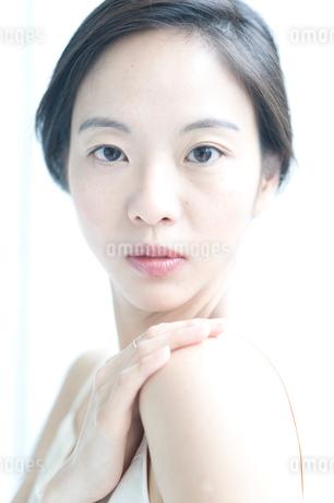 右手を左肩にのせた黒髪の女性 アップの写真素材 [FYI02460173]