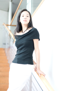 階段でポーズする長い黒髪の女性の写真素材 [FYI02460176]