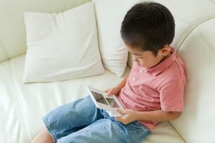 携帯ゲーム機で遊ぶ男の子の写真素材 [FYI02464199]
