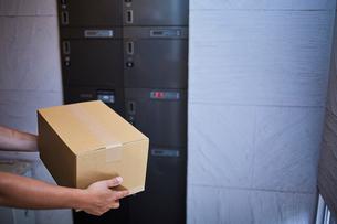 宅配ボックスの前に立つ段ボール箱を持った男性の写真素材 [FYI02464597]