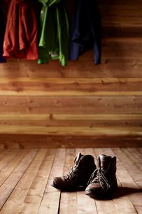 山小屋の中に置かれたトレッキングシューズとフックに掛けられた登山用ウェアの写真素材 [FYI02464625]