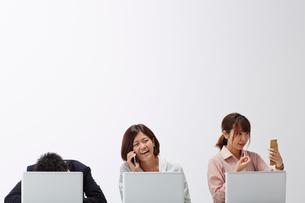 パソコンの前に一列に並んで座る3人の男女の写真素材 [FYI02464673]