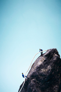 ロープを使って岩を登る2人の男性の写真素材 [FYI02464690]
