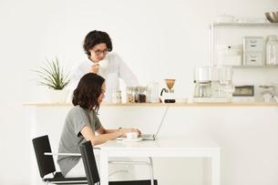 ダイニングキッチンでパソコンをする男女の写真素材 [FYI02464705]