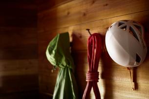 山小屋の中のフックに掛けられた登山用のウェアとロープとヘルメットの写真素材 [FYI02464740]