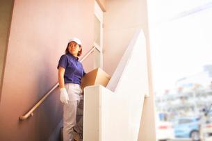 マンションの階段で立つ作業服の女性の写真素材 [FYI02464798]