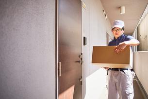 段ボールを持って玄関の前に立つ作業服の男性の写真素材 [FYI02464838]
