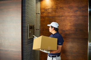 マンションのインターホンを押す作業服の男性の写真素材 [FYI02464840]