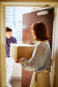 玄関先で段ボールを渡す作業服の男性と受け取る女性の写真素材 [FYI02464870]