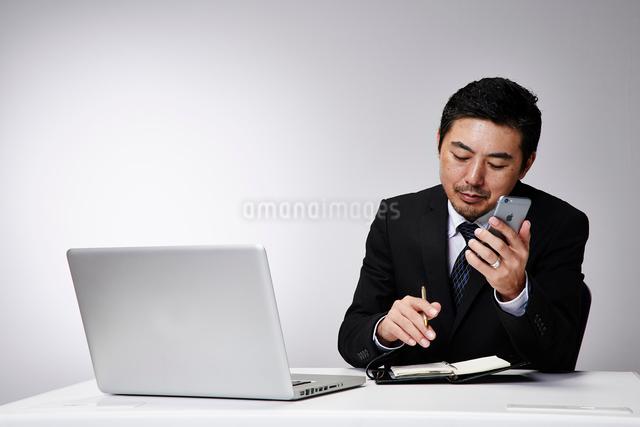 会社のデスクで仕事をする男性の写真素材 [FYI02465022]