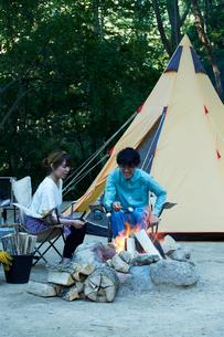 たき火を囲ってマシュマロを食べる男女の写真素材 [FYI02465060]
