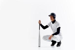バットを持って座っている野球のユニフォームを着た男性の写真素材 [FYI02465084]