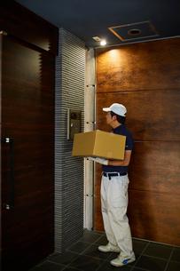マンションのインターホンを押す作業服の男性の写真素材 [FYI02465129]