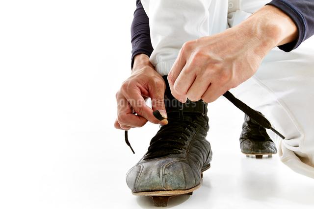 靴の紐を結ぶ野球のユニフォームを着た男性の写真素材 [FYI02465155]