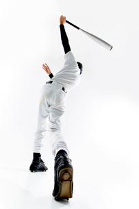 バットを振る野球のユニフォームを着た男性の写真素材 [FYI02465176]