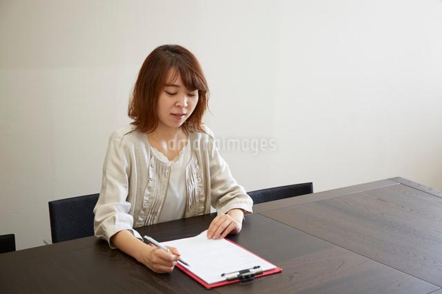 デスクで書類とペンを持つ女性の写真素材 [FYI02465226]