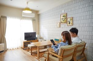 リビングのソファに座ってタブレット端末を操作する女性の写真素材 [FYI02465234]