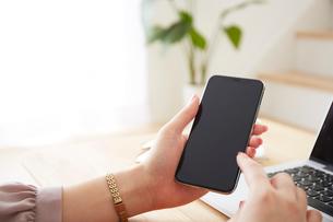ノートパソコンを操作しながらスマートフォンを持つ女性の写真素材 [FYI02465238]