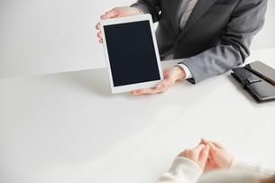 タブレットを使ってお客さんと商談するサラリーマンの写真素材 [FYI02465265]