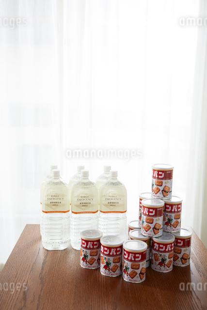 テーブルの上に置かれた保存用の水とカンパンの写真素材 [FYI02465269]