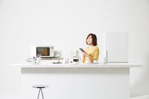 キッチン家電のまわりでスマートフォンを持つ女性の写真素材 [FYI02465294]