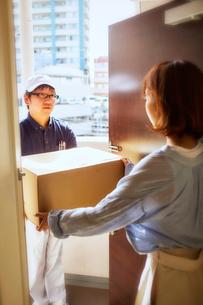 玄関先で段ボールを渡す作業服の男性と受け取る女性の写真素材 [FYI02465299]
