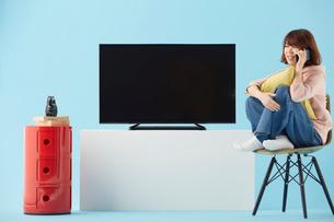 テレビと電話する女性の写真素材 [FYI02465317]