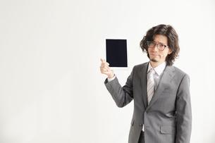 タブレットを持って相手に見せるサラリーマンの写真素材 [FYI02465332]
