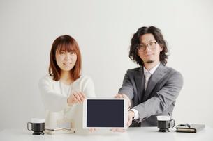 タブレットを使って会議で発表する女性とサラリーマンの写真素材 [FYI02465345]