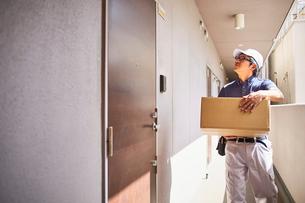玄関の前に立つ段ボール箱を持った男性の写真素材 [FYI02465353]