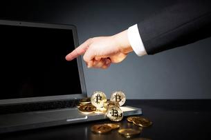 ビットコインとパソコンと指をさすスーツを着た男性の写真素材 [FYI02465380]