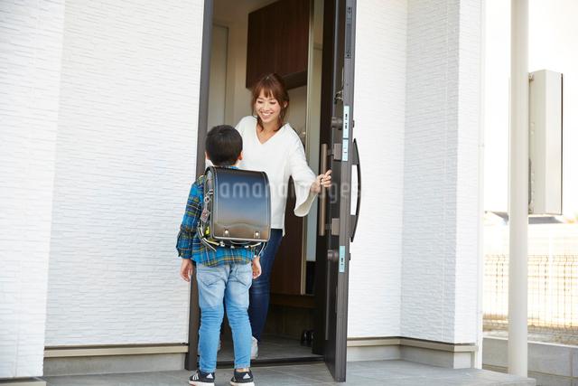子供の帰りを出迎えるお母さんの写真素材 [FYI02465426]
