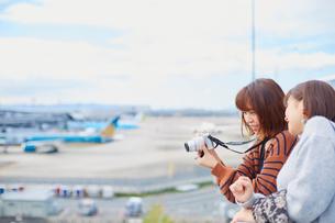 飛行場で飛行機の写真を撮り談笑する二人の女性の写真素材 [FYI02465446]