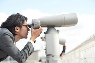 望遠鏡を覗くサラリーマンの写真素材 [FYI02465457]