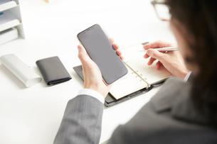 スマートフォンを利用しながら仕事をするサラリーマンの写真素材 [FYI02465474]