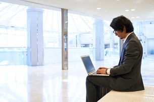 空港でノートパソコンを開くサラリーマンの写真素材 [FYI02465489]