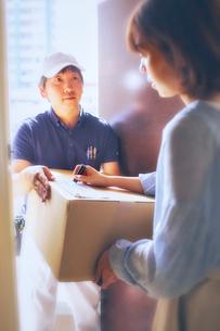 玄関先で段ボールを渡す作業服の男性と受け取る女性の写真素材 [FYI02465552]