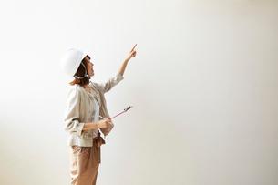 ヘルメットを被り書類を持ちながら指をさす女性の写真素材 [FYI02465574]