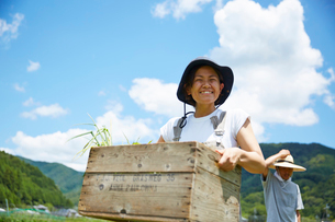 野菜を入れた木箱を持つ笑顔の女性の写真素材 [FYI02465606]