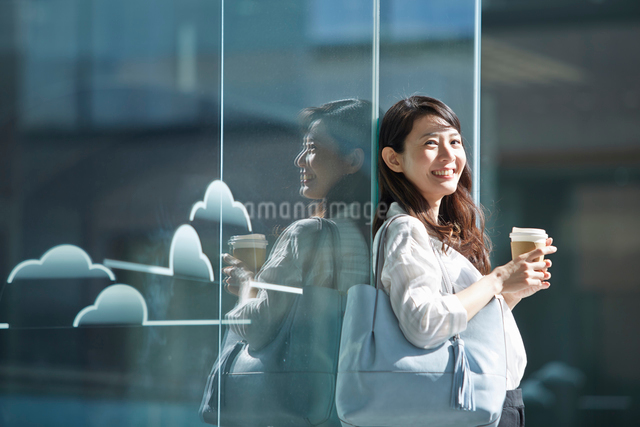 コーヒーを持って立つ笑顔の女性の写真素材 [FYI02465656]