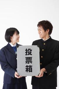 投票箱を持って微笑み合う学生の写真素材 [FYI02465778]