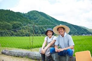 水田の前で丸太に腰掛ける笑顔の男女の写真素材 [FYI02465998]
