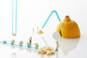 白い天板の上のレモンとビタミン剤とミニチュア人形の写真素材 [FYI02466085]