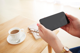 リビングルームでスマートフォンを操作する女性の写真素材 [FYI02466130]