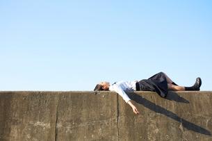 堤防に仰向けで寝る女子高生の写真素材 [FYI02466131]
