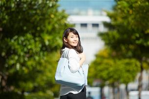 外の道を歩きながら振り返る女性の写真素材 [FYI02466192]