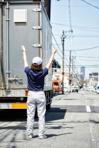 大きなトラックを誘導する働く女性の写真素材 [FYI02466198]