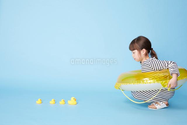 浮き輪に入ってアヒルの人形を見つめる女の子の写真素材 [FYI02466245]