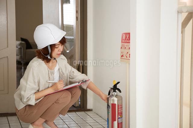 ヘルメットを被り書類を持ちながら点検をする女性の写真素材 [FYI02466300]