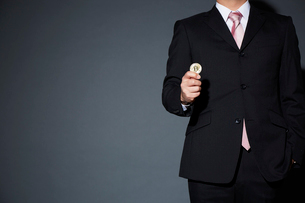 ビットコインを持ったスーツを着た男性の写真素材 [FYI02466422]